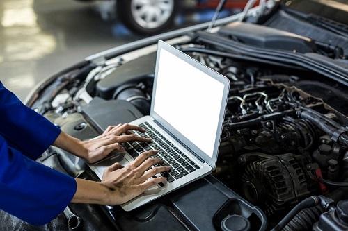 Hands of female mechanic using laptop
