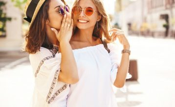 Fashion portrait of two young stylish hippie brunette and blond women in summer sunny day in white hipster clothes posing on the street background. Models share secrets, gossip.